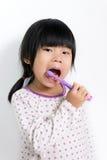 Child brushing teeth. Little Asian girl in pyjamas brushing teeth royalty free stock image