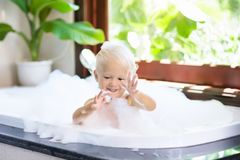 Child in bubble bath. Kid bathing. Baby in shower. Stock Images