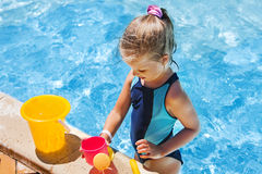 Child with bucket in swimming pool Stock Photography