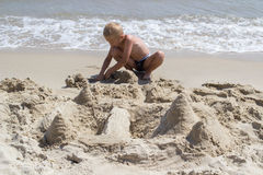 Child build a castle in the sand Royalty Free Stock Images