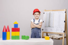 Child Builder builds a house on the drawing Stock Photography