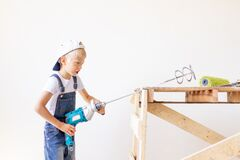 A child Builder holds a construction mixer against the background of a white wall and a construction ladder, a place for text, a