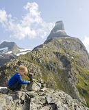 Child building a cairn. Little boy (3) making a cairn, Romsdalshorn in the background. Rauma, Norway Stock Images