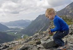 Child building a cairn. Little boy (3) making a cairn. View towards Aandalsnes, Rauma, Norway Royalty Free Stock Photography