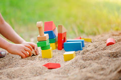Child building house from wooden blocks in sandbox in summer Royalty Free Stock Photo
