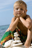 Child building pyramid from pebble. Stock Images