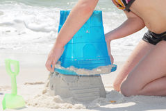 Child building sand castle. Young girl on pretty beach building sand castle stock image