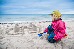 Child building sand castle near the ocean Royalty Free Stock Photos