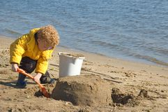 Child Building Sandcastle. Little boy (3) with shovel, building a sand castle on the beach Royalty Free Stock Photo