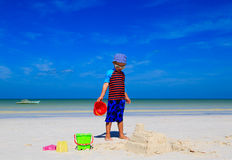 Child building sandcastle on tropical beach Stock Images