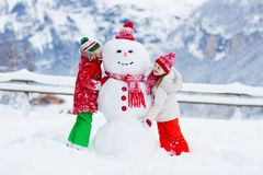 Child building snowman. Kids build snow man. Boy and girl playing outdoors on snowy winter day. Outdoor family fun on Christmas vacation in the mountains stock images
