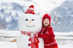 Child building snowman. Kids build snow man. Boy and girl playing outdoors on snowy winter day. Outdoor family fun on Christmas vacation in the mountains royalty free stock photos