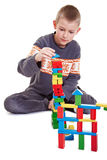 Child building a tower. Boy building carefully a tower with building bricks Royalty Free Stock Photos