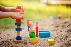 Child building toy houses of colorful wooden bricks in sandbox Stock Image