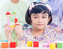 Child building wooden house. Muslim child building wooden house. Southeast Asian girl playing woodblock house at home royalty free stock images