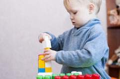 Child builds a pyramid with  colored plastic constructor Stock Photo