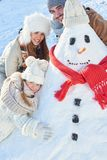 Child builds snowman with her family Stock Images