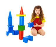 Child builds a toy castle on floor Royalty Free Stock Image