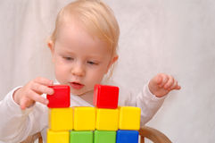 Child builds a wall. The child builds a wall of cubes Royalty Free Stock Photo