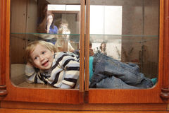 Child in built-in closet. The smiling child in a built-in closet royalty free stock photo