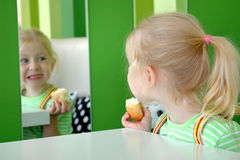 Child with bun peers into mirror. In cafe Royalty Free Stock Photo