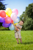 Child with a bunch of balloons in their hands Royalty Free Stock Photo