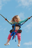 Child on bungee trampoline. Toddler having fun on a bungee trampoline against blue sky Stock Photo