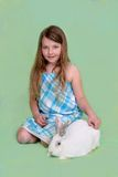 Child with bunny. One young pretty child with a white bunny over a pastel colored background Royalty Free Stock Images