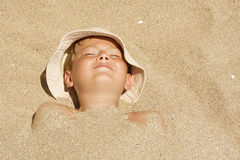 Child buried in the sand. Portrait of a boy buried in the sand Stock Photos