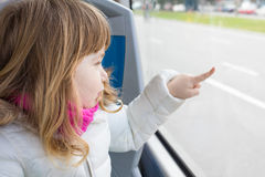 Child in bus touching glass window with finger Stock Photos