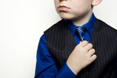 Child in Business Suit Holding Tie. A child in a blue business suit with hand adjusting tie Stock Photo