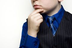 Child in Business Suit Thinking. A child in a blue business suit thinking with hand holding chin Royalty Free Stock Photos