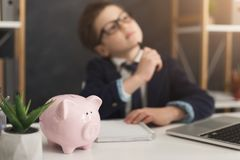 Child businessman dreaming of income. Pensive little businessman thinking of income at office table with piggy bank, selective focus stock photography