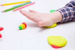 Child busy playing with plasticine on a white table Stock Photography