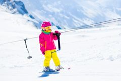 Child on ski lift in snow sport school in winter mountains. Child on a button ski lift going uphill in the mountains on a sunny snowy day. Kids in winter sport royalty free stock photos