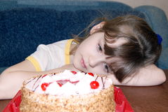 The child with a cake. The girl with grief looking at a pie Stock Photography
