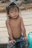 Child in Cambodia. Poor cambodian kid sitting on floor of Bayon Temple, Siem Reap, Cambodia Stock Photography