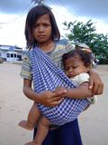 Child on Cambodian Thai border. CAMBODIA BORDER, THAILAND - OCTOBER 07: Young Cambodian girl carries her sister and begs for money on the Thai Cambodian border Stock Image