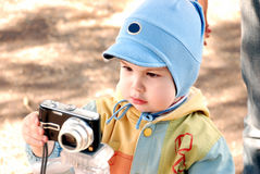Child and camera. The child photographies on a nature in the spring Stock Photo