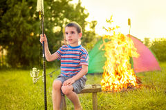 Child on a camping trip learning how to; use fishing rod. Camp in the tent -boy on the camping Stock Image