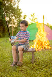 Child on a camping trip learning how to; use fishing rod. Camp in the tent - young boy on a camping Stock Photo