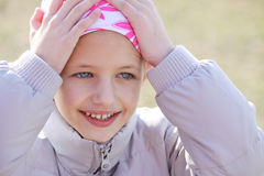Child with cancer. Child wearing head scarf due to hair los from chemotherapy treatment due to cancer Royalty Free Stock Images