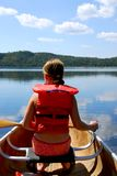 Child in canoe. Paddling on a scenic lake Stock Photos