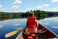 Child in canoe. Young girl in canoe paddling on a scenic lake Stock Photography