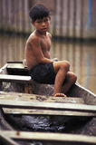 Child on canoe in the Amazon, Brazil. Child on a canoe in the Amazon, after the flood of the Rio Purus. Labrea, Amazonas, Brazil Stock Image