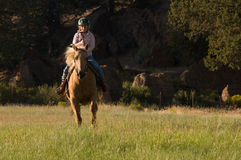 Child Cantering on Palomino. A child cantering on a palomino horse toward the camera with boulders and trees in the background Stock Photography
