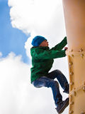 The child in a cap and jacket pipe climbs up Stock Photos