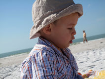 Child with cap playing  in sand. On the beach Stock Photos