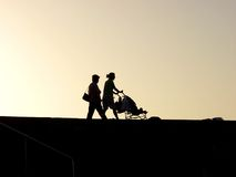 Child car. A woman walking whit child and grandmother at sunset Stock Photography