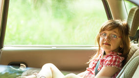 Child in car. Holidays vacation trip travel. Little girl child kid in glasses with seat belt fastened sitting in car. Holidays vacation trip. Safe summer travel Stock Image